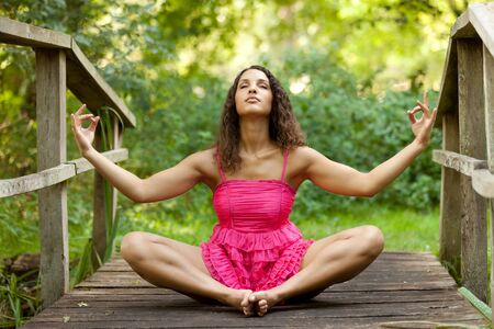 young woman sitting on wooden bridge in lotus position photo