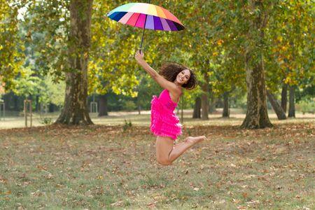 rainbow umbrella: girl jumping in park holding a rainbow umbrella Stock Photo