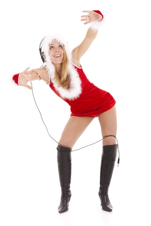 glamor santa girl listening music and dancing  with earphone and cable around legs photo