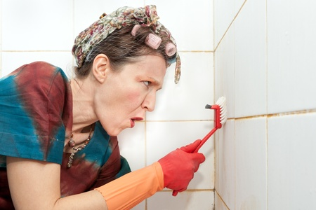 funny angry woman using brush to wash shower tiles