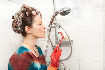 funny woman cleaning bathroom shower with brush Stock Photo - 9466978