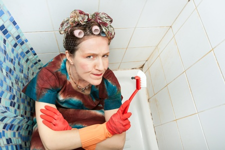 funny angry woman making a face while cleaning bathroom tiles photo