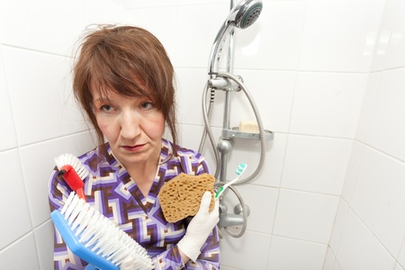woman holding brushes very bored to clean bathroom shower photo