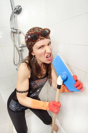 eccentric hippie woman singing with brush in shower photo