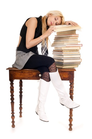 glamour schoolgirl sitting on wooden table sleeping on book stack photo