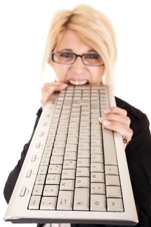 exasperated: dynamic view of furious business woman biting computer keyboard