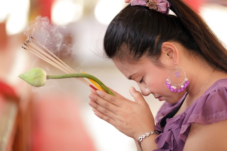 buddhism: young asian woman praying buddha holding lotus flower and incense stick, thailand