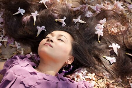 young asian woman sleeping among flowers under sunlight