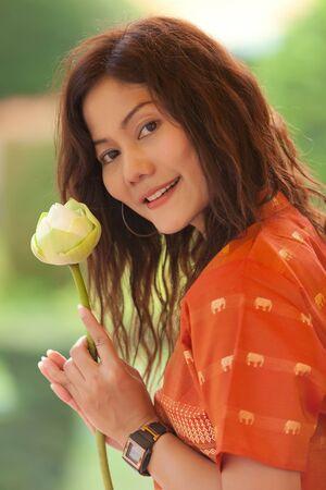 cute asian woman holding lotus flower for praying buddha photo