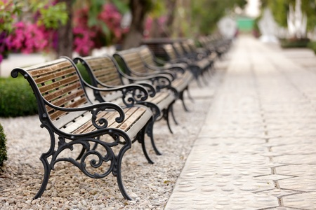public park: metallic and wooden bench in a row, shallow deep of field selective focus on the first Stock Photo