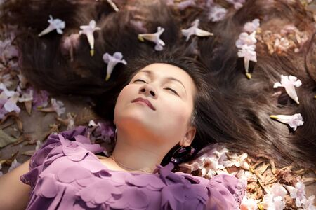asian woman lying in purple flowers with sunlight photo