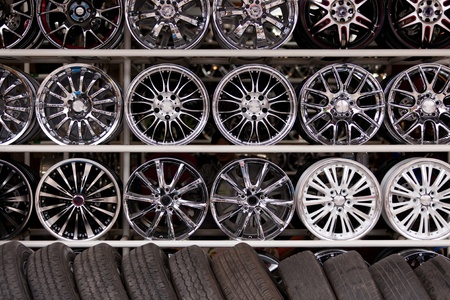 pneumatic tyres: wall of alloy car wheels and pneumatic tires in store