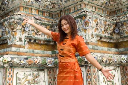 asian woman making welcome gesture near wat arun temple wall, bangkok photo
