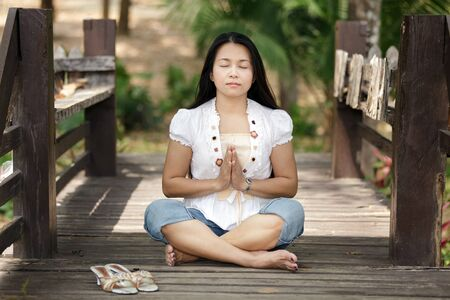 asian woman praying in lotus position on wooden bridge photo