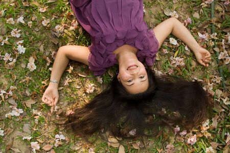 happy asian woman lying on grass and smiling photo