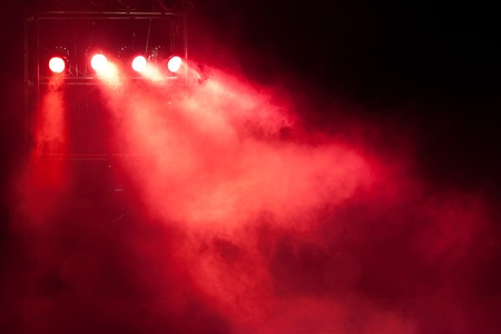concert stage with red spot light and smoke photo