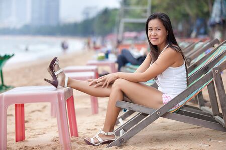 asian woman sitting on reclining chair, thailand photo