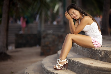happy asian woman sitting on stairs, Pattaya, Thailand photo