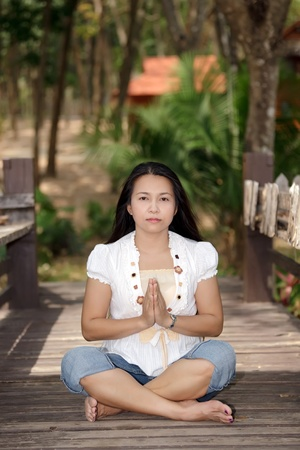 asian woman meditating on wooden bridge in park photo