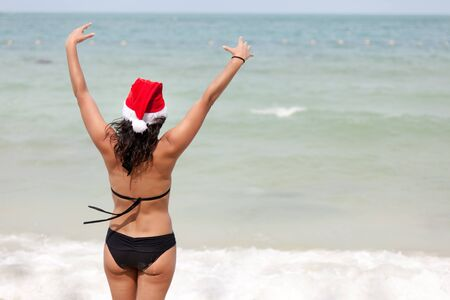 beautiful woman wearing santa claus cap raising arms at tropical beach photo