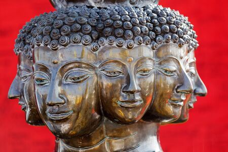 multi headed metallic buddha head on red background, thailand photo