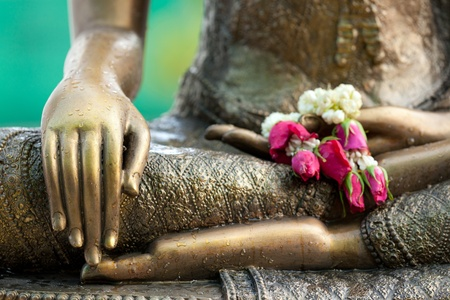 golden buddha statue detail with flower offering and water drops Stock Photo