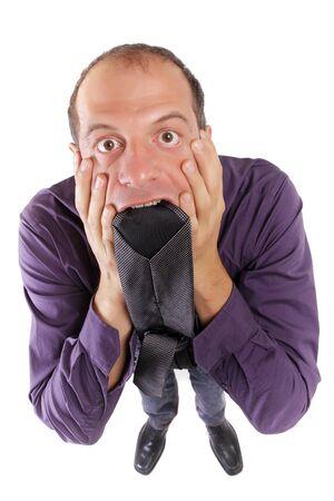 desperate: hombre de negocios de frustred morder su corbata aislado en blanco Foto de archivo