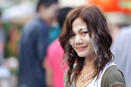 beautiful asian woman, face covered with wet powder during songkran new year festival in thailand photo