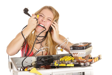 broken telephone: upset bond woman trying to repair computer and biting power cord