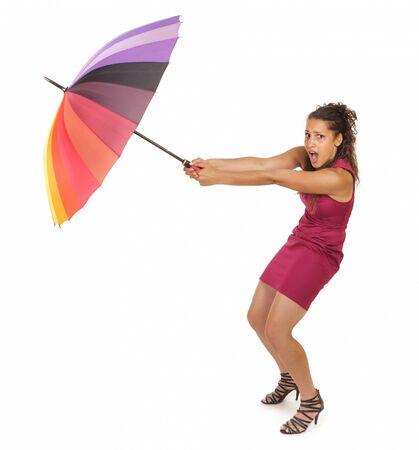 mujer que sostiene colorido combates paraguas con tiempo ventoso Foto de archivo