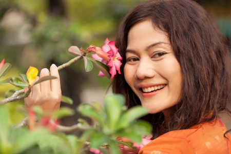 asian woman face: close portrait of asian woman looking pink flower