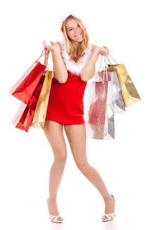 christmas shopper: happy young woman in santa suit carrying shopping bags