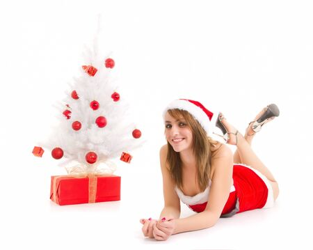 young woman in santa suit lying near christmas tree and gift photo