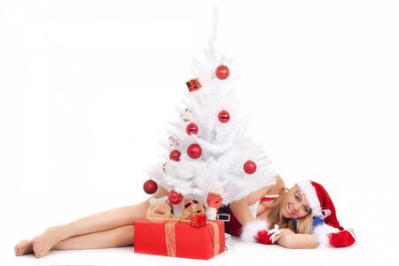 christmas woman lying on floor near ornate tree and gift Stock Photo - 10447367
