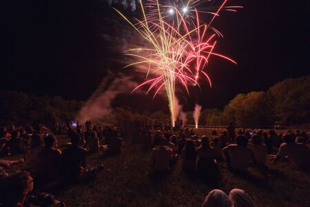 spectacle: people sitting and watching fireworks display in field Stock Photo