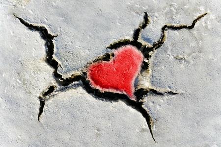 corazon roto: forma de corazón rojo natural en suelo seco craqueado