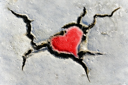 natural red heart shape in cracked dry soil photo