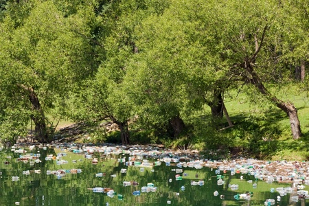 excretion: tons of plastic container floating on lake water surface, Bicaz lake, Romania Stock Photo