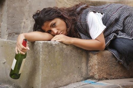 drunk young woman holding botle of wine lying on stone stairs