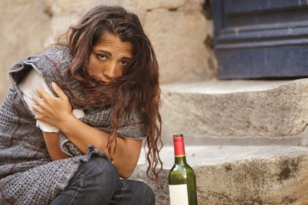 alcoholic drinks: poor homeless drunk woman in cold weather