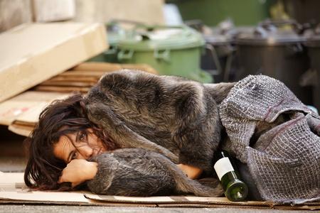 hobo: young tramp woman lying among trash with bottle of wine