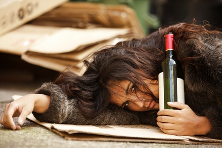 drunk tramp woman holding bottle of wine and lying on pavement photo