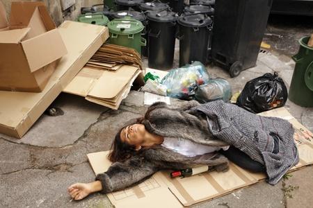 dronken zwerver vrouw, liggend op karton in de stad prullenbak gebied Stockfoto