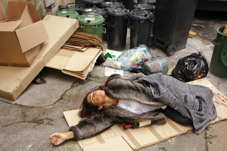 tramp: drunk tramp woman lying on cardboard in city trash area
