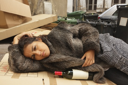 vagrant: young hobo woman lying on city pavement with bottle of wine