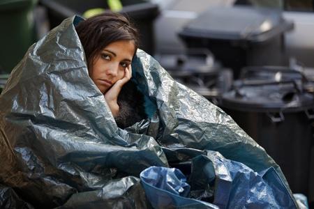dakloze jonge vrouw verpakt in plastic zeil in koud weer Stockfoto
