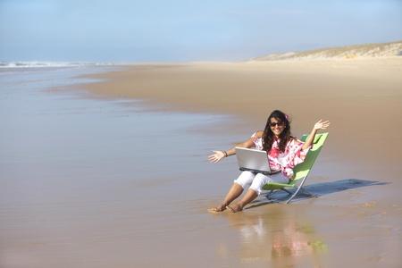 opgewonden vrouw met behulp van laptop op wilde strand