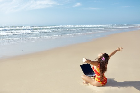 woman relaxing and using laptop on wild beach photo