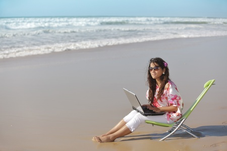 young woman relaxing and using laptop on wild beach photo
