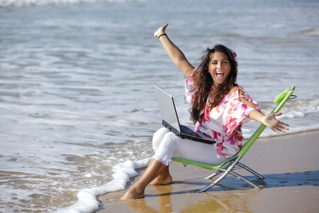 ecstatic: excited woman  using laptop on wild beach Stock Photo